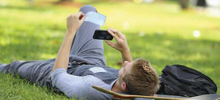 Man laying down in the grass taking a picture of a check with his mobile device